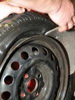 Obrázek - technik vyzouvá pneumatiku propíchnutou z boku.